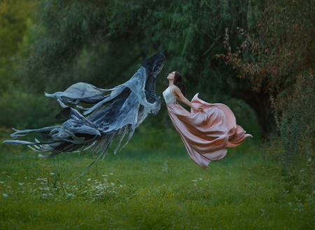 young slender princess with dark hair and neat haircut wore a long luxurious fluttering flying dress dancing in the air next to a terrible demon in a quiet forest. creative warm colors. art photo