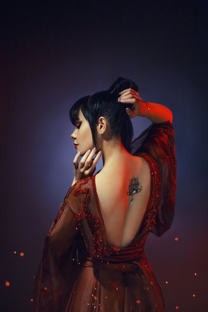Japans gorgeous sexy tender dark-haired princess, young samurai woman in light red dress with deep neckline and lotus tattoo on her back. art photo with blue background and orange flare of fire