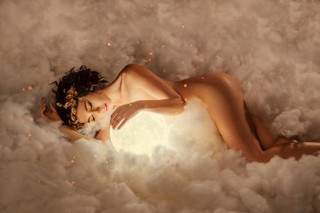 de nacht en dag godin slaapt in de wolken, als in een dikke witte mist, omhelst de volle maan, een meisje met een gouden krans en make-up, met kinderachtig onschuldig gezicht in de gloed van vuur Stockfoto