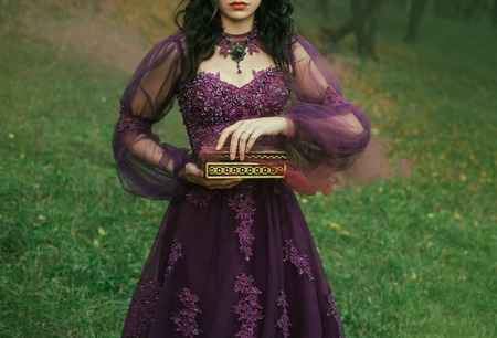 a dark-haired young lady holds in her hands an open Pandoras box, the red maroon thick fog of evil and disease slowly comes out, as a punishment for humanity. gothic image, art photo without a face