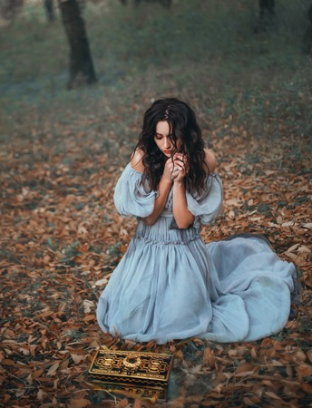 Pandora opened the damn casket and let out a terrible curse outside, the girl in horror removes her hands from the box, making a fatal mistake. lonely dark girl in gray vintage dress in forest