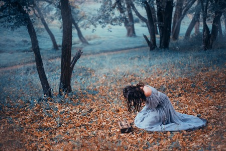 dark-haired girl in a long, light gray, old-fashioned dress, sits on cold ground covered with autumnal fallen leaves, in a dark forest, crying over Pandora's open box. no face on art photo, depersia