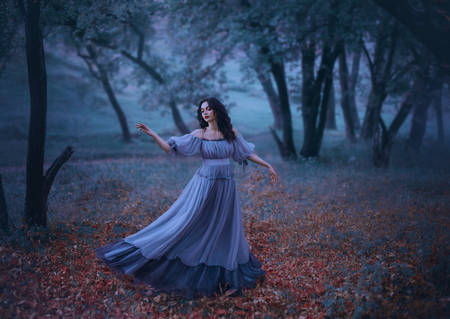 a mysterious girl with wavy dark hair is dancing alone on fallen autumn leaves in a gloomy night forest in a long wonderful blue vintage dress, fabulous heroine, knows no ills, the legend of Pandora 版權商用圖片