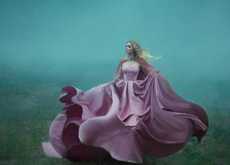 blonde in the fog in a light long expensive royal dress fluttering on the fly, takes the form of a magic flower, a delightful photo in motion. an excerpt from the life of a fantastic character girl Stok Fotoğraf