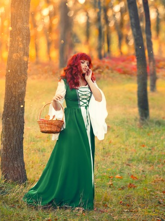 Red-haired bavarian lady walks across the field and gathers her hands