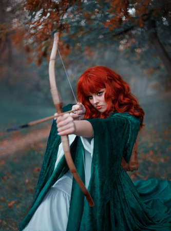brave red-haired girl holds a bow in her hands, directing an arrow, experienced hunter goes into battle, warlike image of the princess in emerald cloak and white dress, art in cold colors, Gothic fog