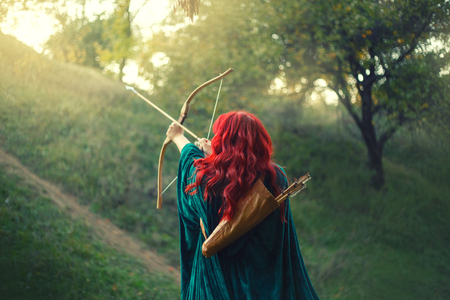 gorgeous huntress pushing her last light to the sun, waiting for salvation during terrible danger, red-haired girl fights bravely for life, emerald velvet cloak, photo without a face from the back