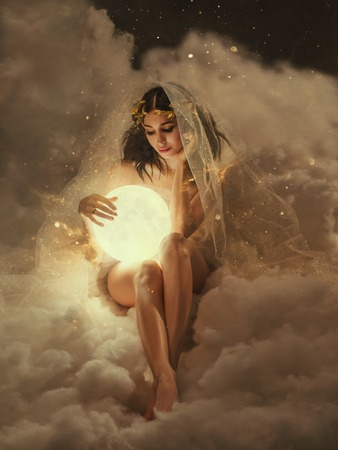 gorgeous slender sexy lady sits in the clouds and holds the moon in her hands. daughter of the sun and sky, keeper of dreams, ready to do good and a fairy tale under the cover of night and the stars Stock Photo
