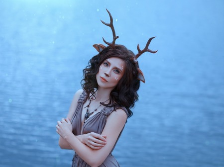 girl in the image of a faun, costume and make-up of a deer, a fantastic character of the spirit of forest in brown dress, portrait photo of a sad lady on background of magical lake, blue cool shades Stock Photo