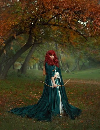 red-haired beauty in search of the victim, the legend of Robin Hood, mysterious lady in green velvet long raincoat with arrows and bow in her hands, fearless girl ready for battle in a foggy forest