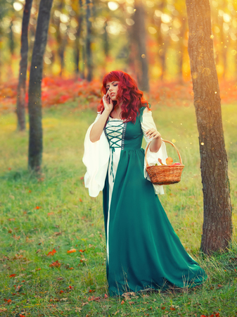 girl with fiery red hair, an unusual appearance, in an emerald white gorgeous delightful dress, holds a basket and explores new paths of the forest, a bright photo in the glare of the morning sun