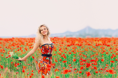 cute attractive blonde is standing in the field, bright red scarlet poppies, a clear bright sky with a lot of free space, a positive stylish photo in the summer season, warm colors. Reklamní fotografie