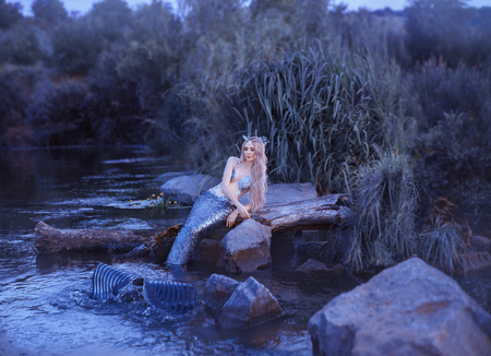 charming slender mermaid lying on the stones in the river evening water, a blonde with a sea wreath on her head and a long tail with scales, creates waves with a fin, queen of the underwater world