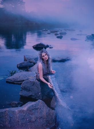 attractive slender mermaid sits on the rocks by the river in a thick blue purple magic fog, brushes her long tail and scales, dives the fin into the water, a wonderful crown of shells on her head Imagens