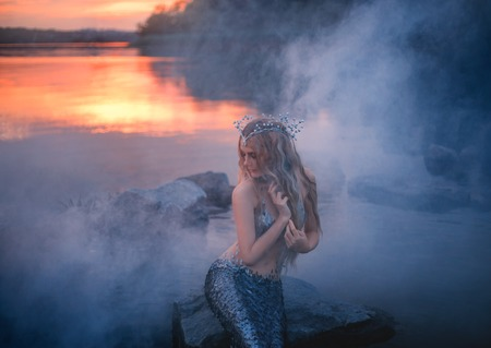 sea maiden with long blond hair, shell tiara sits in thick fog, combs her hair with fingers, evening sunset makes orange reflection in the clear water of the lake, a magical siren with a silver tail