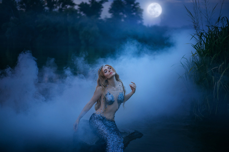 Neptunes daughter absorbs and eats moonlight, the magnificent sea ruler sits on a stone in the night river and rests in a thick fog, a fabulous character with art processing photos Imagens