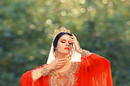 charming delightful Turkish lady in bright red scarlet light dress puts her hands to a gorgeous face, mistress Roksolana with amazing expensive luxury crown on dark hair, gold jewelry and ornaments