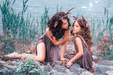 faunas mother and child are sitting on the rocks on the bank of the river, the parent looks after her baby, the girls are dressed in long brown dresses with a violet tint, horned fairy creatures