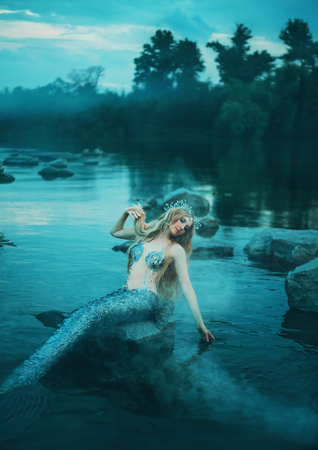 pretty cute mermaid girl with long blond hair and silver scaly tail sits on a stone in the middle of the lake and plays with her hand, a beautiful fairytale nymph in an early cool morning alone
