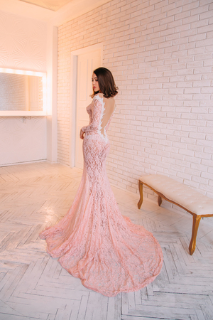 Luxurious brunette girl, with a bob haircut, posing in an expensive, pink dress with an open back. The princess in the white room. Scandinavian minimalist style interior. Image for prom and party Stock Photo