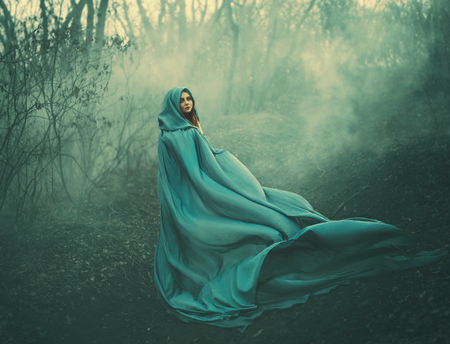 attractive large lady in long blue summer light waving raincoat runs through forest with bare trees and mysterious white smoke and magical fog, charming sorceress escapes from a fairytale monster Stockfoto