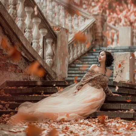 great-looking charming dark-haired brunette girl sitting alone on the stone steps of an amazing royal castle, pretty magician in a long elegant golden dress playing with autumn leaves
