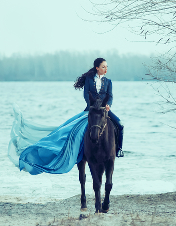 gorgeous countess in a strict blue suit and high leather boots, hot cheeky girl with Amazon skirt with long flying train, princess on a black horse, confident brunette with long curled hair