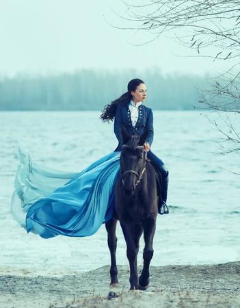 splendida contessa in un rigoroso abito blu e alti stivali di pelle, ragazza sfacciata calda con gonna amazzone con lungo treno volante, principessa su un cavallo nero, bruna sicura con lunghi capelli ricci