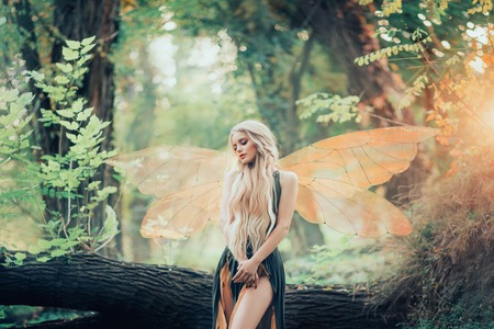real fairy from magical stories, goddess of nature with transparent wings alone in dense forest, beauty closes her eyes, listens to birds singing, charming lady in the sunlight and with bare legs