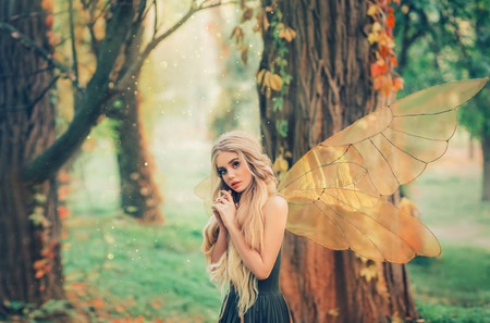bright summer photo with shining rays of sun, mysterious forest fairy fell in love with prince, girl with puppet face, blond long hair and blue eyes, lady in green dress peeps modestly, with interest