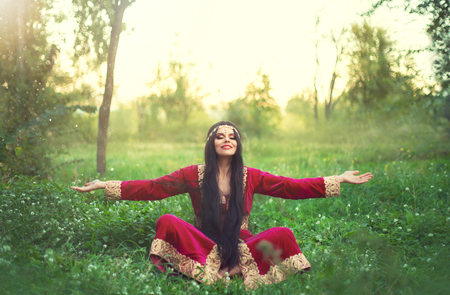 charming brunette girl in long burgundy maroon dress on grass in summer glade, wonderful Valida rests, meditates, enjoys sun, time of the Ottoman Empire, positive emotions, gold jewelry and tiara Stock Photo