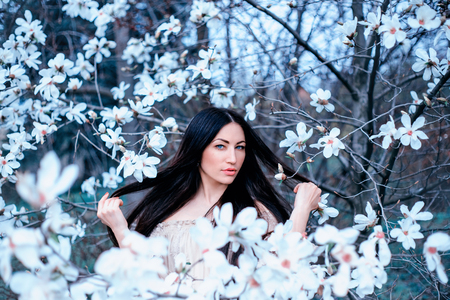 a delightful young dark-haired blue-eyed lady stands in the garden of blooming magnolias. hair flies up with her hands, amazing photo in cold shades of white filter, art processing photo