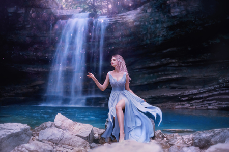 attractive sexy water fairy with sad face, fantastic nymph near lake in Georgia, Martvili Canyon nature. tender girl with long blue flying dress, pink hair. creative art processing, creative colors Stock Photo