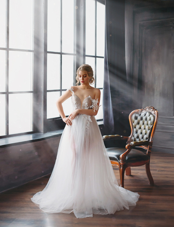 charming excellent lady became bride, girl with blond gathered hair tries on wedding chic white luxurious light dress in spacious room with large windows and bright light, naked gentle shoulder