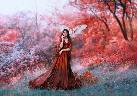 powerful autumn nymph, queen of fire and goddess of hot sun, lady in long red light dress with loose sleeves with dark hair, model in scarlet forest with flying owl, bloody Mary, vampire image 스톡 콘텐츠