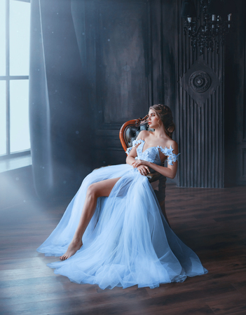 majestic and proud princess girl in white chic oriental blue dress tired sitting on chair, lady shows off her slender leg and waiting for prince, gentle stylish image of graduate 2019. Fine art 版權商用圖片