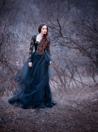 gorgeous attractive brunette, lady in a long black dress with bare open arms and shoulders, the girl alone in the autumn cold forest, the weather in November is a dark princess in the form of raven