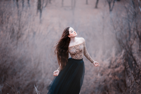 amazing tender brunette, lady in a long black dress with bare open arms and shoulders, the girl alone in the autumn cold forest, the weather in November is a dark princess in the form of crow