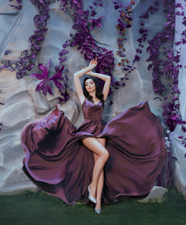 slender attractive lady like picture of gorgeous artist, flying fluttering purple long satin dress like paint strokes, sexy girl elegantly raised her arms top, shows charming bare legs in gray heels Stok Fotoğraf