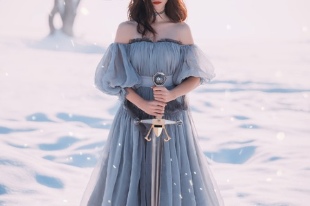 warlike woman with dark hair in long gray vintage light dress and sharp silver sword in hands