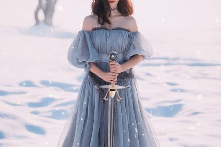 wojownicza kobieta o ciemnych włosach w długiej szarej jasnej sukience z ostrym srebrnym mieczem w dłoniach
