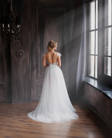amazing lady in long white adorable expensive light dress with train and open back stands with back to camera, girl with blond hair posing in spacious room with large windows with sunlight. no face