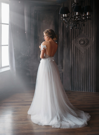 new fairy tale about Cinderella, sweet and gentle lady in amazing wonderful white long dress with open back and straps falling off shoulders, aesthetics of girl with bleed hair in the morning sun