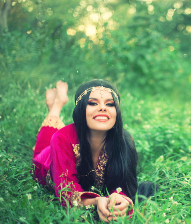happy attractive cheerful woman with long black hair lying on the early grass, bright sunshine and glare, with wide smile resting in meadow, wise healer collects medicinal herbs