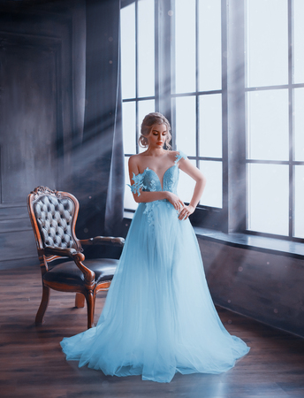 A gentle, snow queen stands by the window in a fabulous dress with bare shoulders. The room is filled with magical rays of moonlight. An image of a young girl for the prom party. Art photography Stockfoto