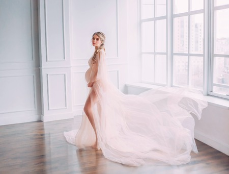 cute young slim lady with tummy in spacious room with white walls and large windows, pregnant girl with blond hair twisted in a long pink gentle lace peignoir with flying train posing for camera Reklamní fotografie