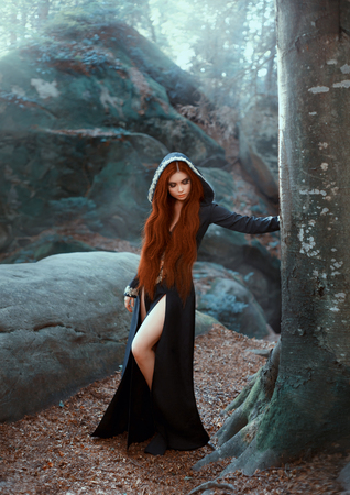 mysterious girl in long black dress with cut for bare legs and hood stands by tree, dark priestess with bright red hair listens to voices of frosty forest, winter ice photo with art processing