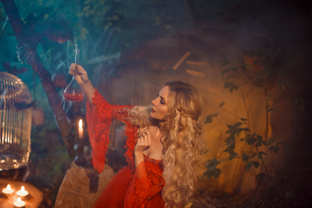 pretty young lady preparing a potion to bewitch her beloved boyfriend, girl with blond curly hair in a long sexy red dress with long sleeves, mysterious forest fairy of love, the daughter of cupid Stock Photo