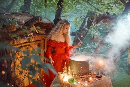 Hübsche junge Dame mit blonden Locken über einem großen Zauberkessel mit Rauch und Flaschen mit Flüssigkeiten, Waldnymphe in langem leuchtend rotem Kleid mit losen Ärmeln bereitet Trank in der Nähe des Holzhauses zu