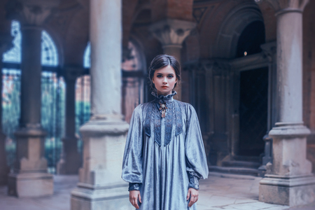 Strict teacher in a gray velvet vintage dress looking into the camera. Overseer psychological wedge strictly mode. Art photography, depressed mood. Background gothic architecture with columns